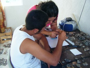 High-school student Luis Manuel learning how to draw sherds from Ely.