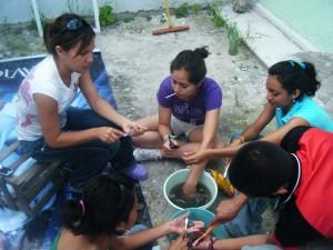 Estudiantes de preparatoria ayudándonos a lavar la cerámica. Para ello, utilizamos cepiilos de dientes, cubetas y agua. Afortunadamente los suelos en esta área no son ácidos, por lo que podemos cepillar las piezas sin peligro de dañarlas.